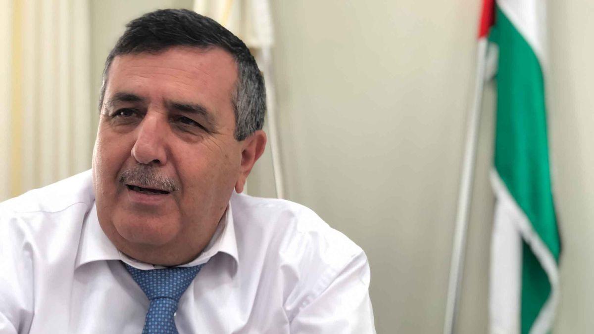 Bürgermeister Antone Salman mit weißem Hemd und blauer Krawatte in seinem Büro vor einer palästinensischen Fahne.