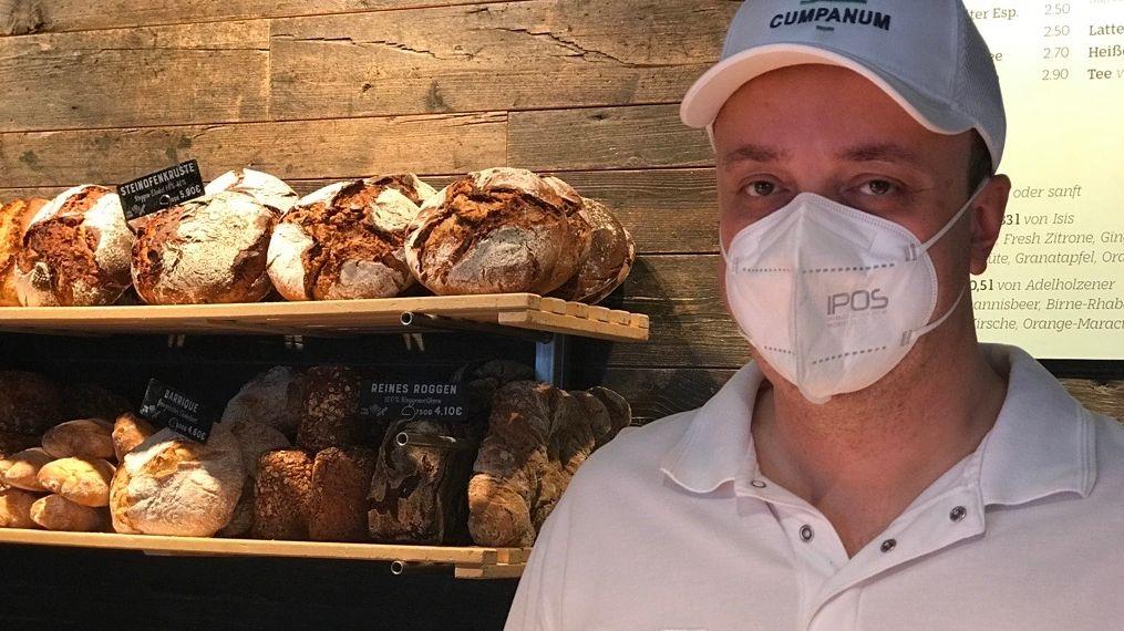 Bäckermeister André Heuck vor verschiedenen Brotsorten im Regal