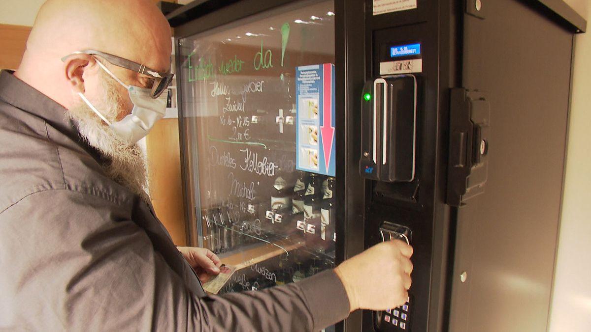 Ein Mann wirft Geld in einen Beirautomaten.