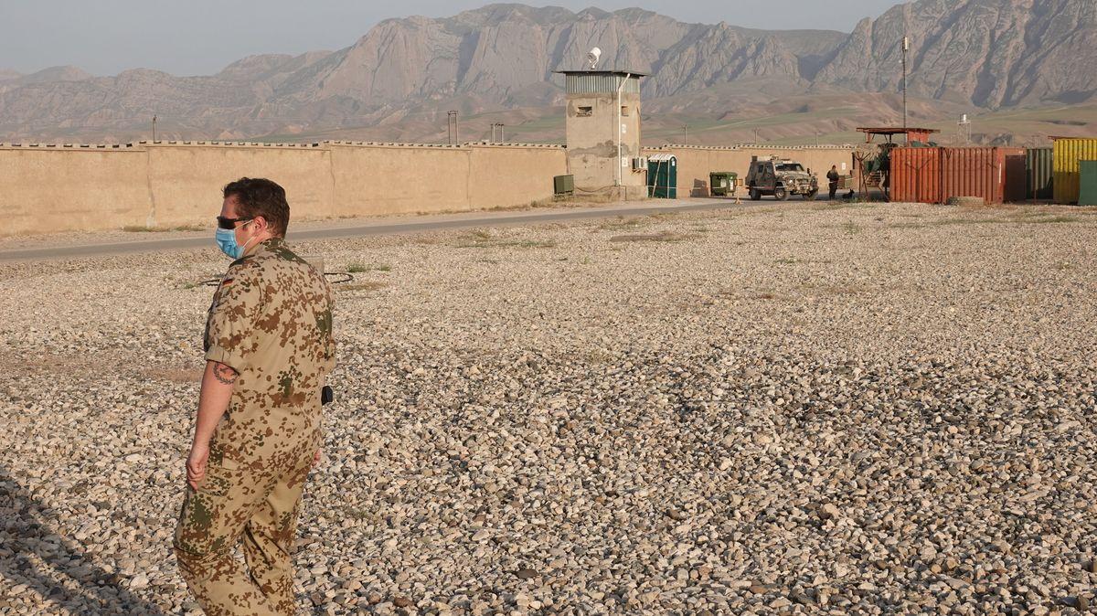 Ein Soldat steht im nordafghanischen Masar-i-Scharif im Camp Marmal vor einer Außenmauer des Camps mit einem Wachturm.