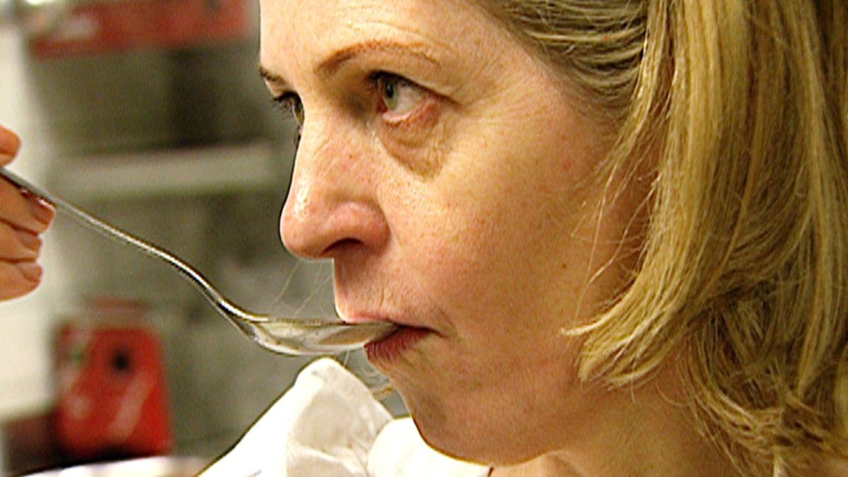 Blonde Frau probiert etwas von einem Löffel.