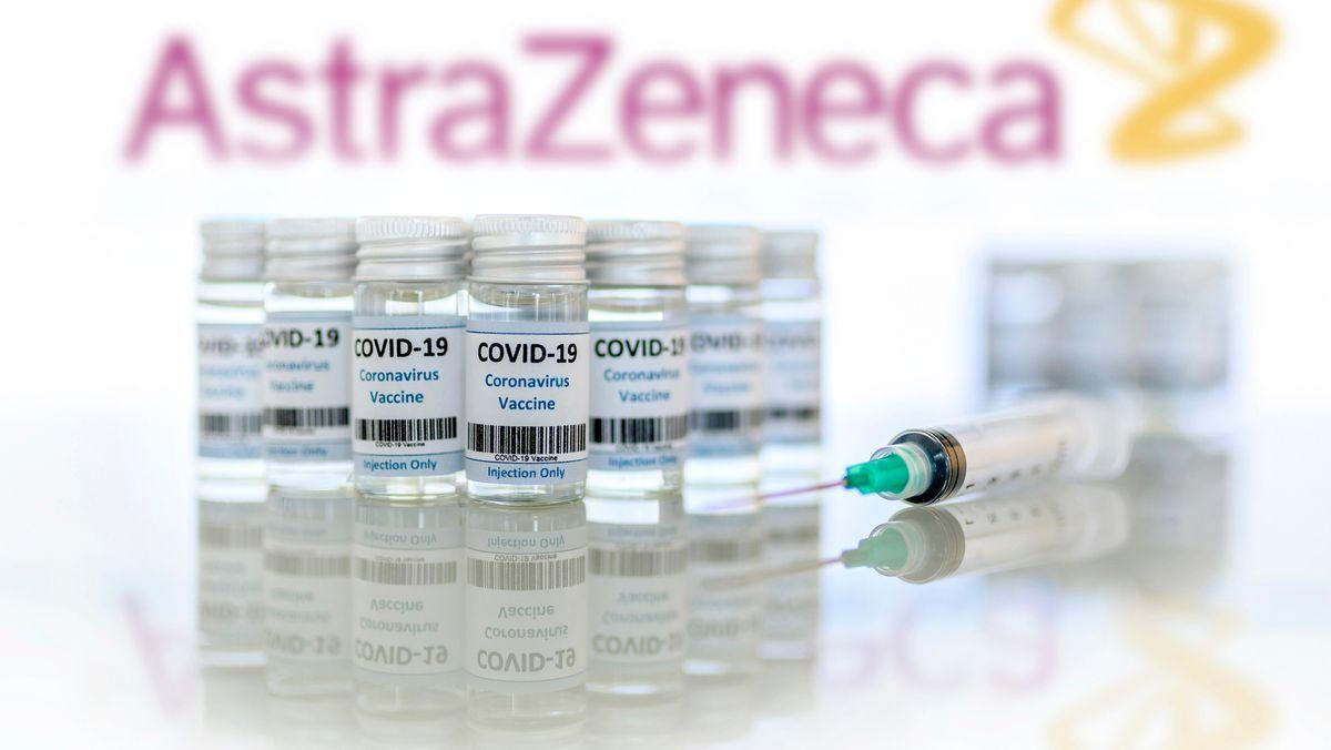 Impfdosen und Impfspritzen stehen auf einem Tisch vor dem AstraZeneca-Logo.