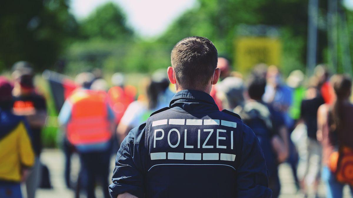 """Polizeibeamter beobachtet die Teilnehmer einer """"Corona-Leugner"""" Demonstration in Heidelberg"""