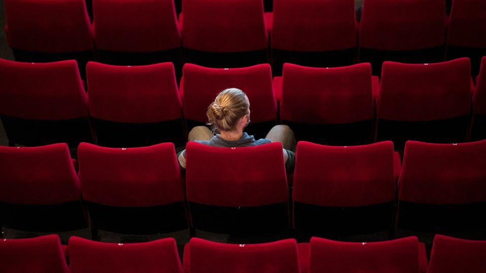 Soziale Distanz: Eine Frau sitzt alleine im Kino
