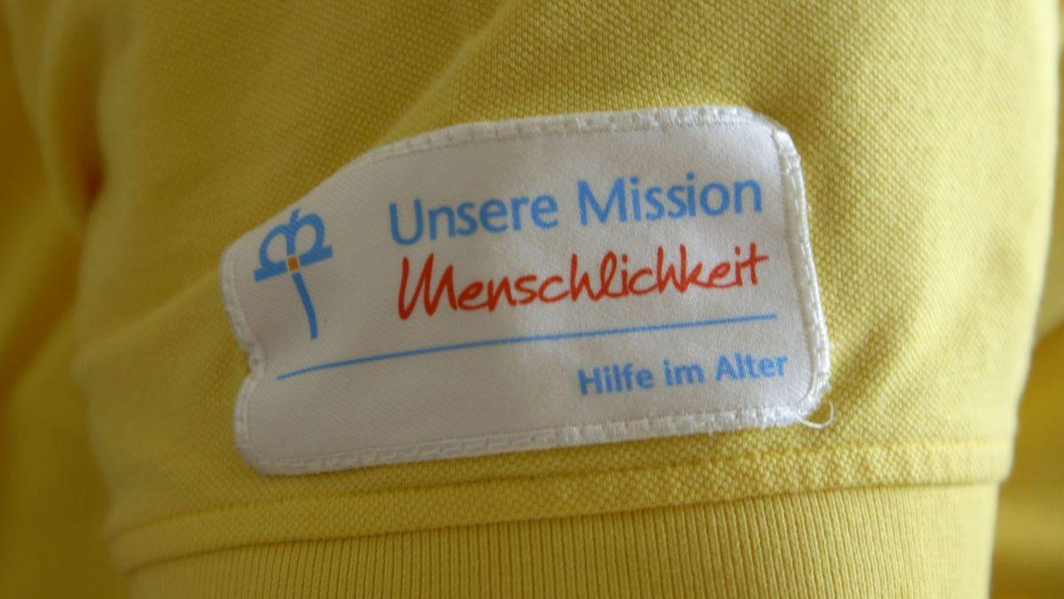 """Aufnäher auf dem T-Shirt einer Pflegekraft: """"Unsere Mission - Menschlichkeit - Hilfe im Alter"""""""
