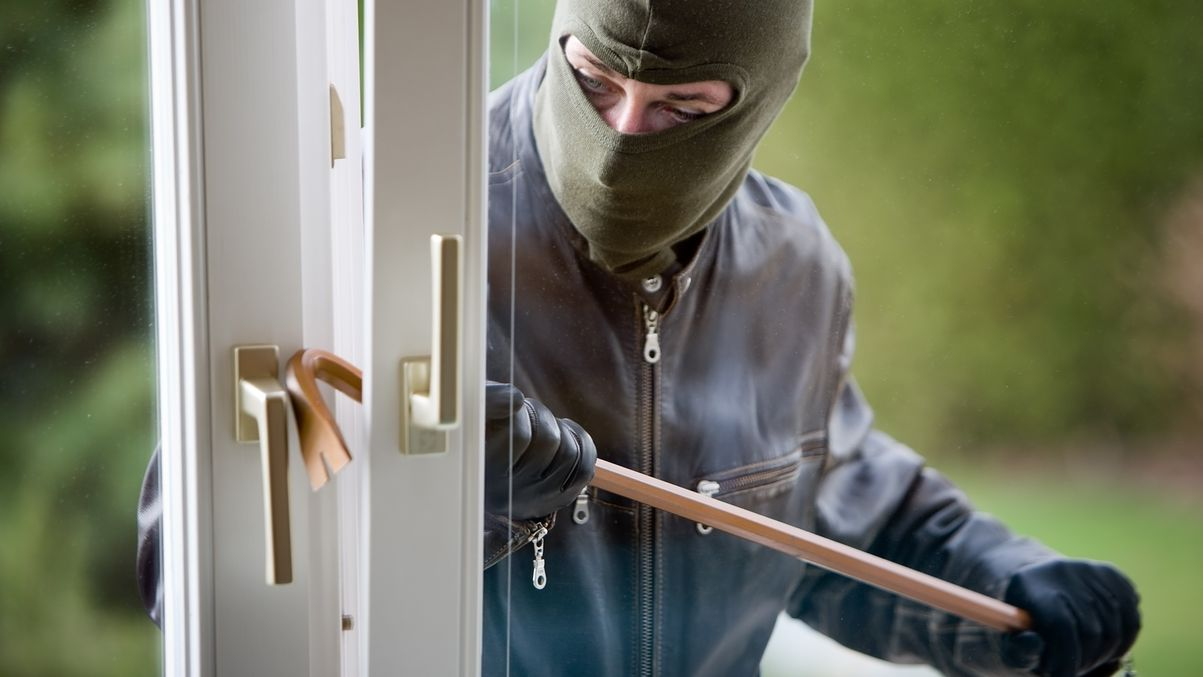 Maskierter Einbrecher knackt mit einem Brecheisen ein geöffnetes Fenster auf.