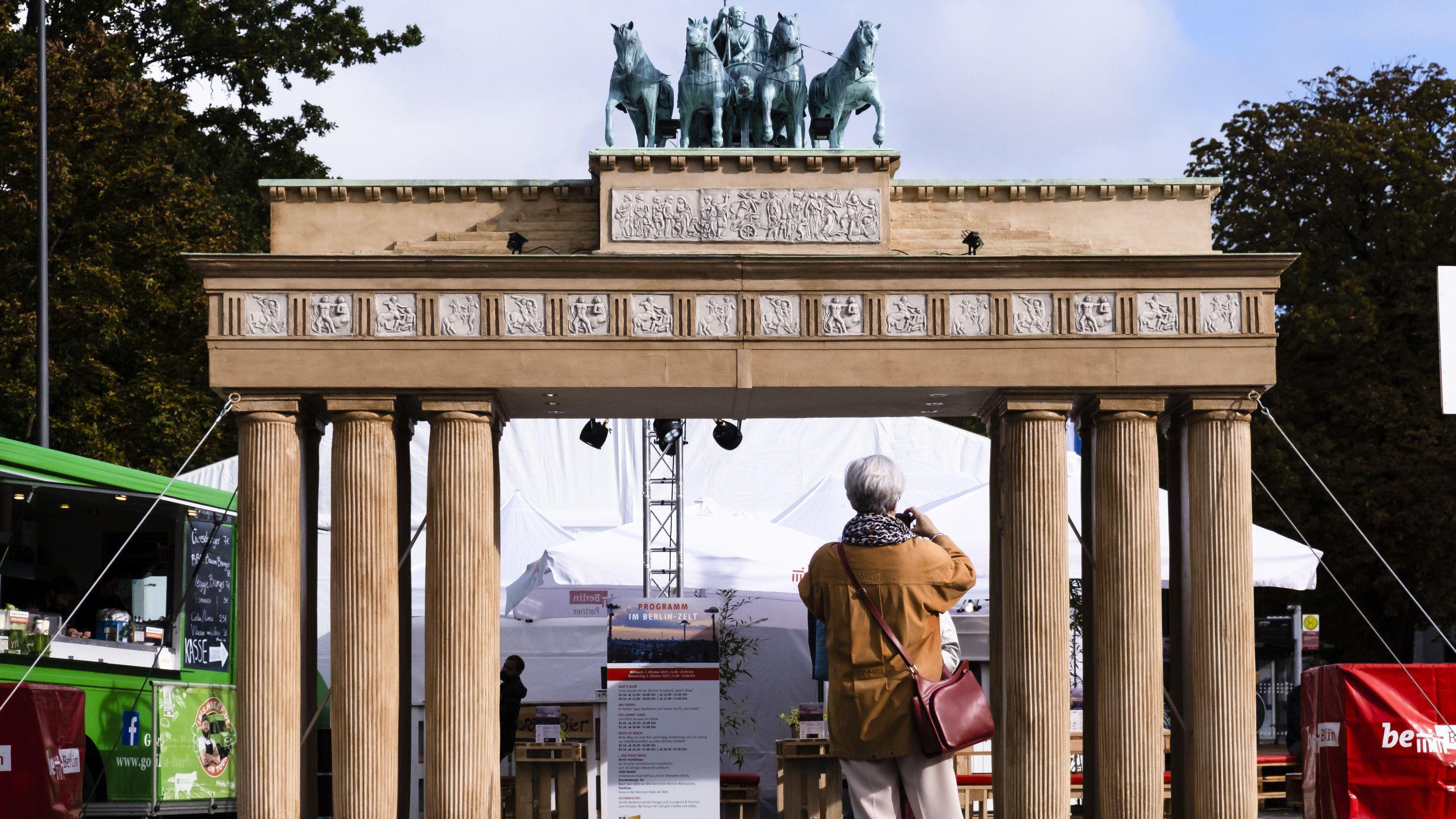 Eine Besucherin fotografiert eine Miniaturausgabe des Brandenburger Tors im Rahmen der zentralen Feier zum Tag der Deutschen Einheit in Kiel.