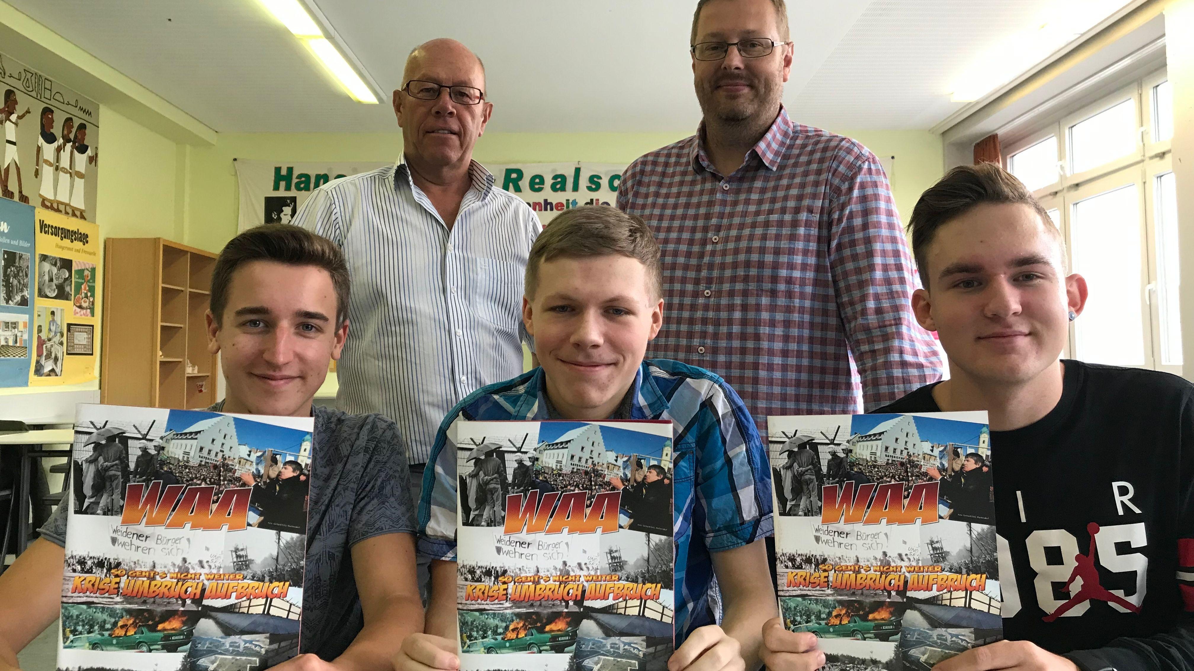 Schüler der Hans-Scholl-Realschule Weiden mit WAA-Comic, dahinter Journalist Gerhard Götz und Lehrer Johannes Paar
