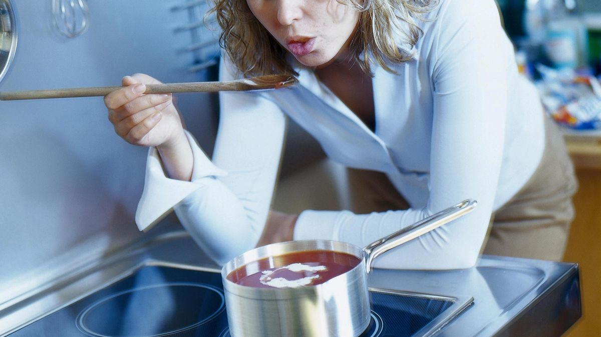 Frau lehnt am Herd und probiert Tomatensuppe mit Kochlöffel