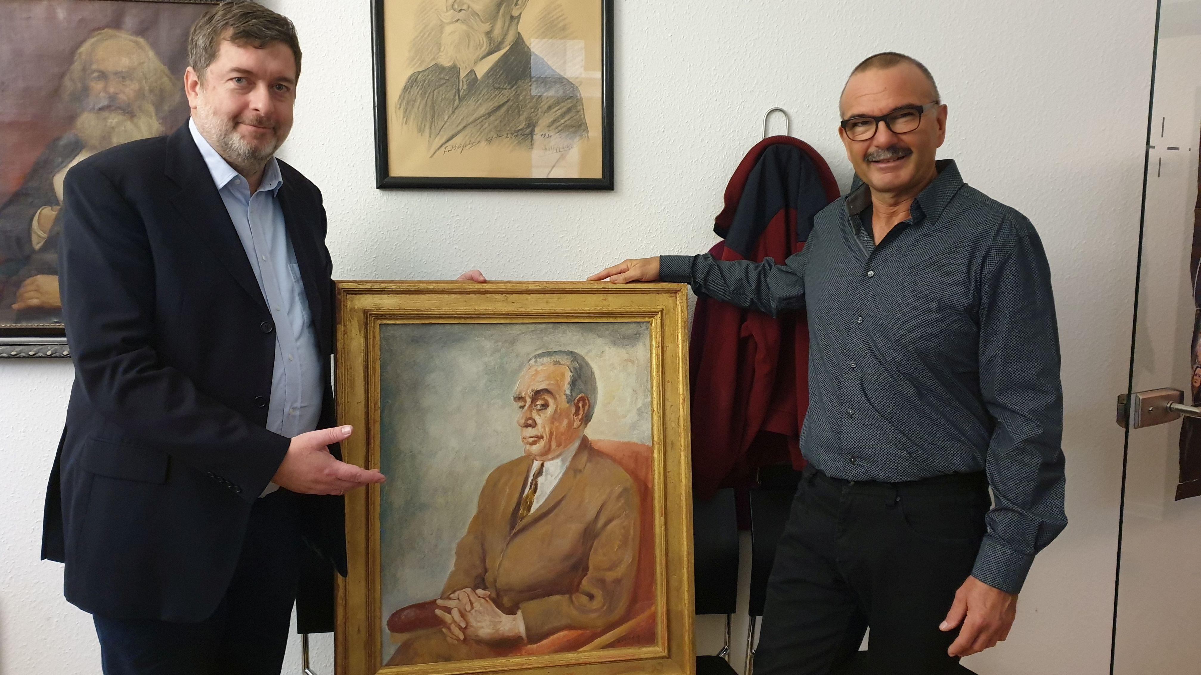 Zwei Männer präsentieren ein Bild das einen Mann im anzug zeigt der auf einem Sessel sitzt.