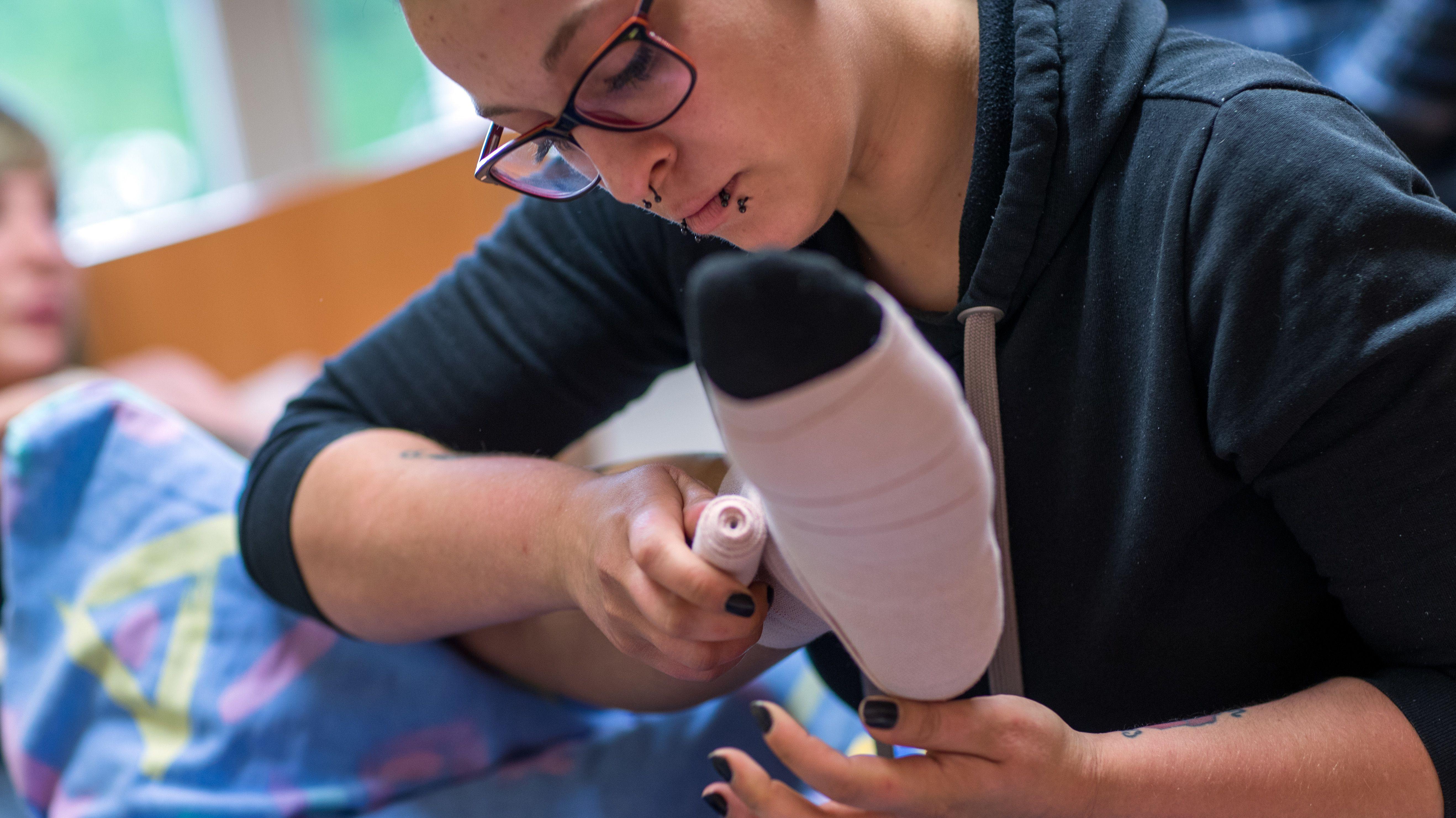 Eine Pflegeschülerin übt bei einer Mitschülerin, einen Thromboseverband anzulegen (Symbolbild
