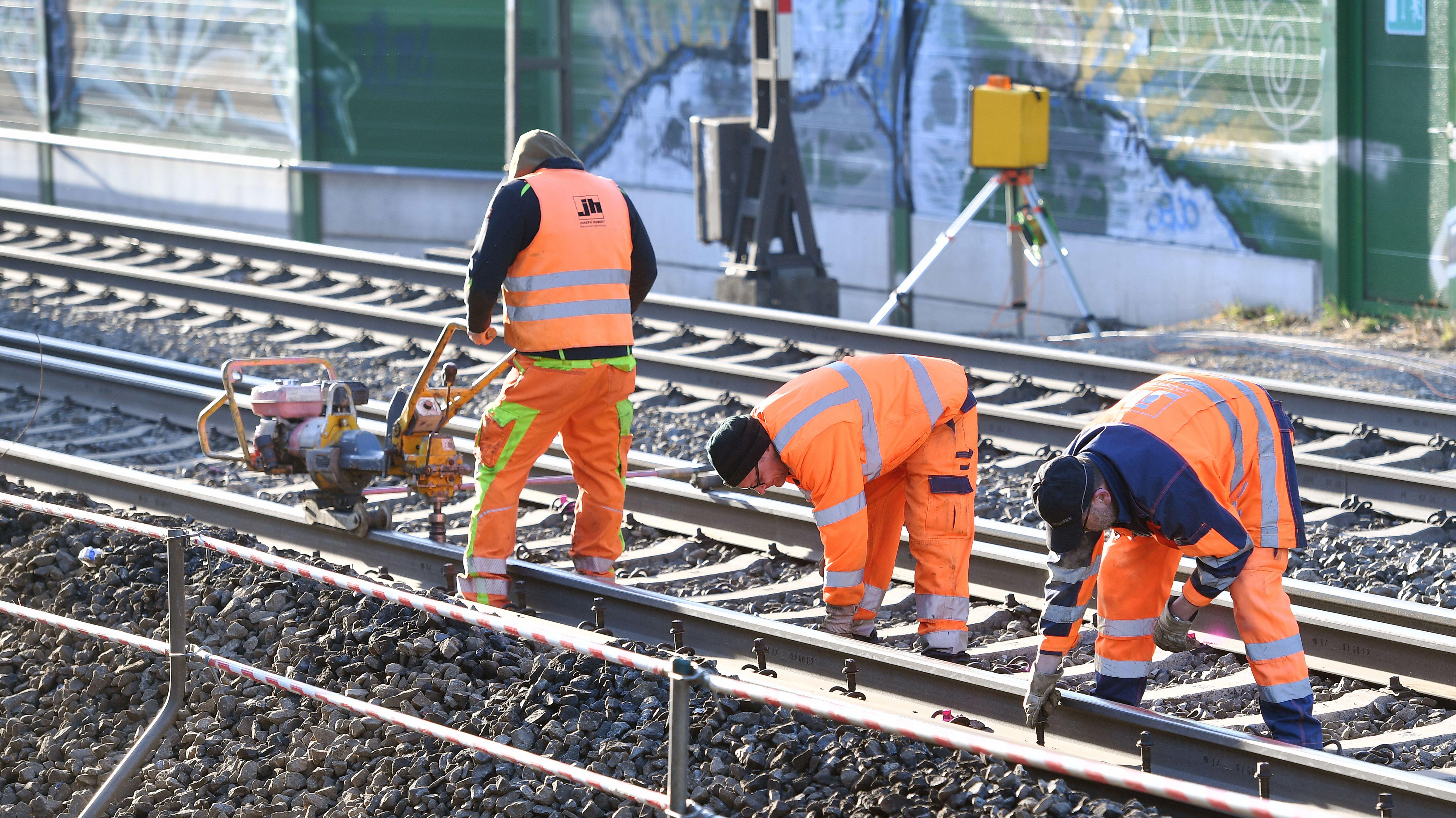 Gleisarbeiter beim Ausbauen von Bahnschienen