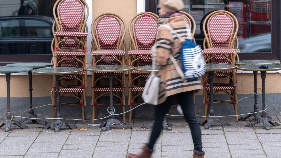 Eine Frau geht an einem geschlossenen Café vorbei.