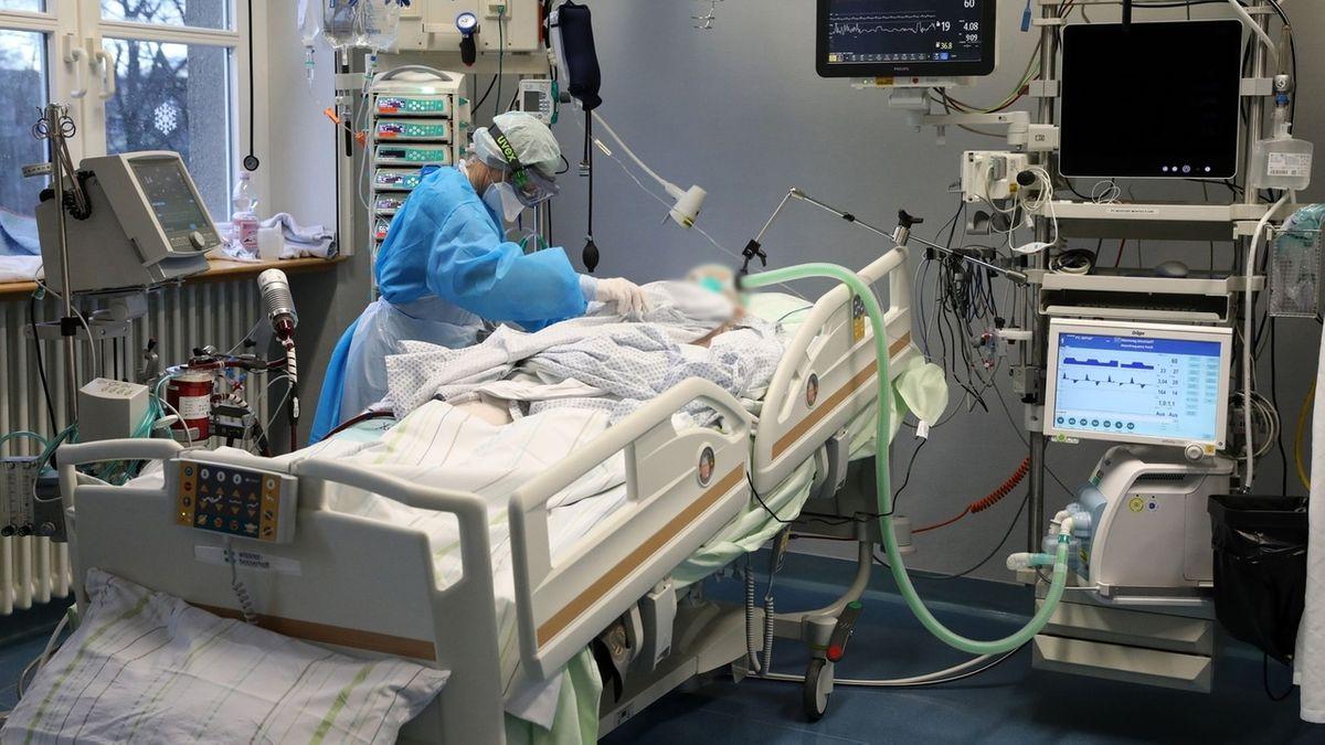 Eine Person pflegt einen Patienten in einem Bett auf der Intensivstation (Symbolbild).