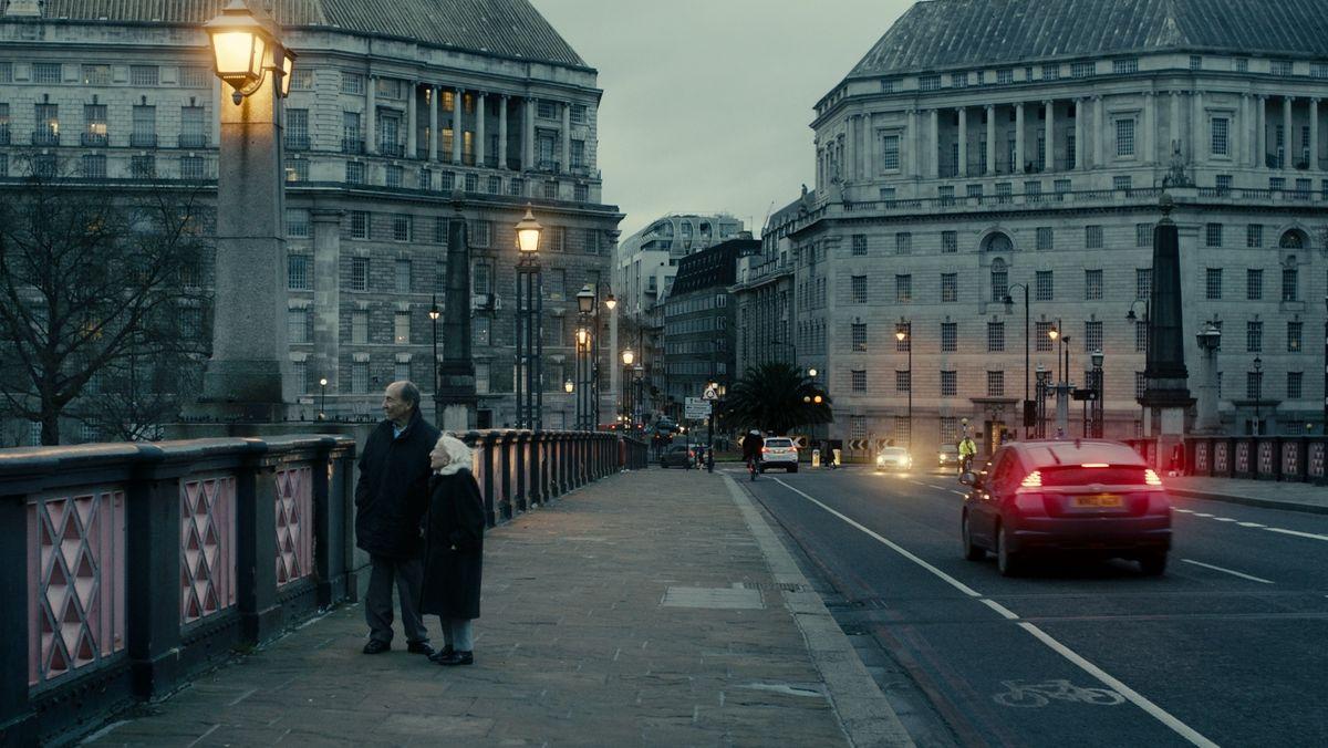 Marthe Cohn in männlicher Begleitung auf einer Brücke in London in der Abenddämmerung.