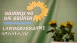 Das Logo des Landesverbandes Saarland Bündnis 90/Die Grünen ist auf einem Transparent auf der der Bühne des Landesparteitages zu sehen. | Bild:dpa-Bildfunk/Oliver Dietze
