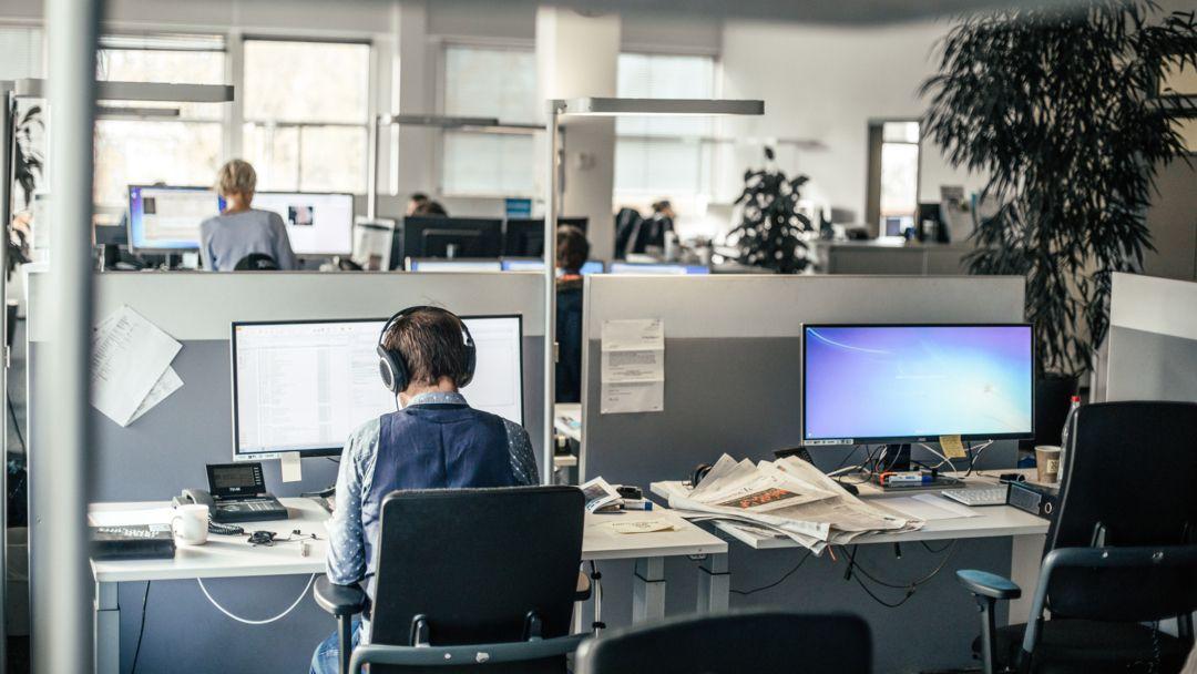 Ein Mitarbeiter sitzt mit Kopfhörern in einem Großraumbüro.