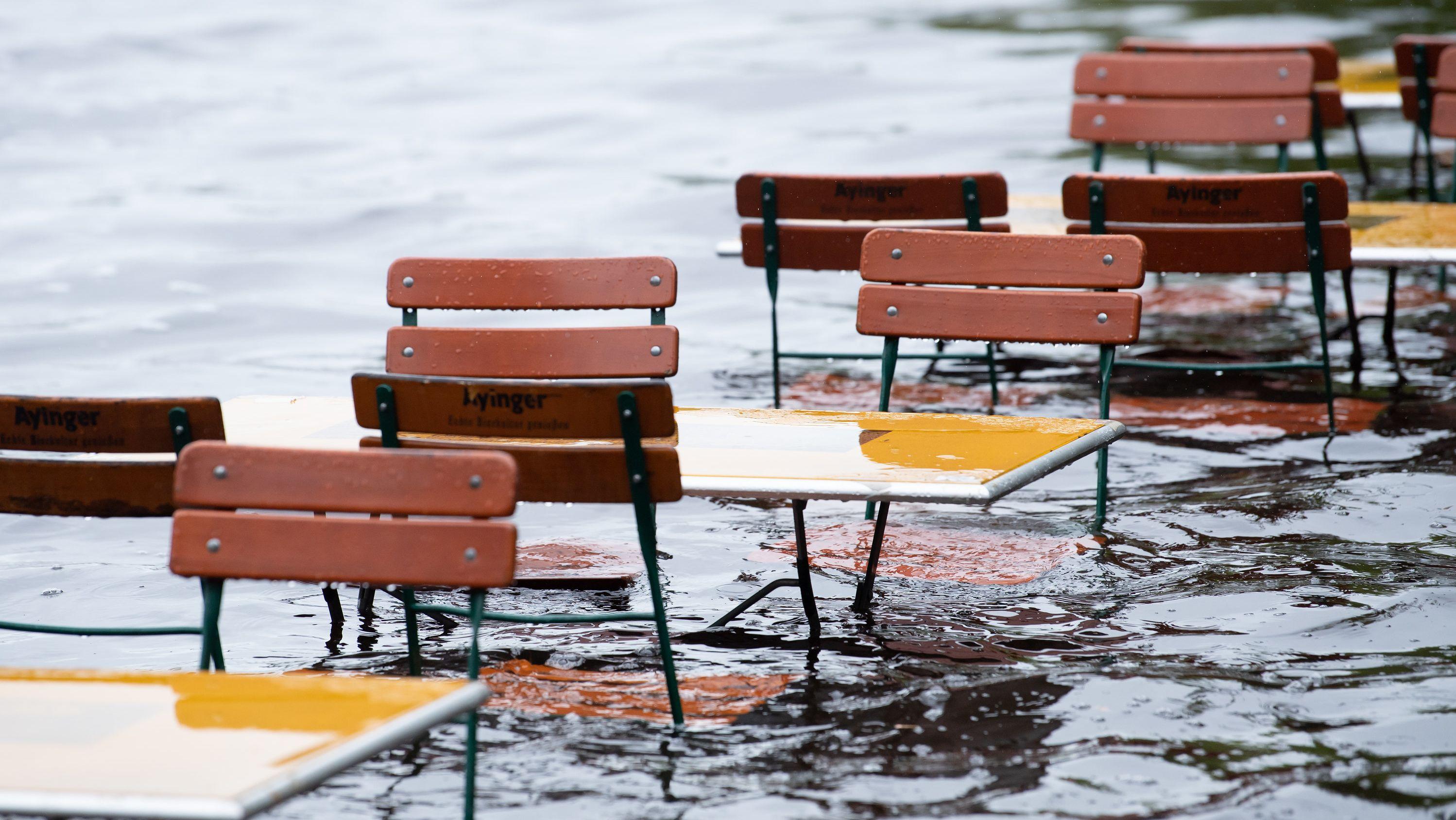 Tische und Stühle eines Biergartens stehen nach starkem Regen unter Wasser