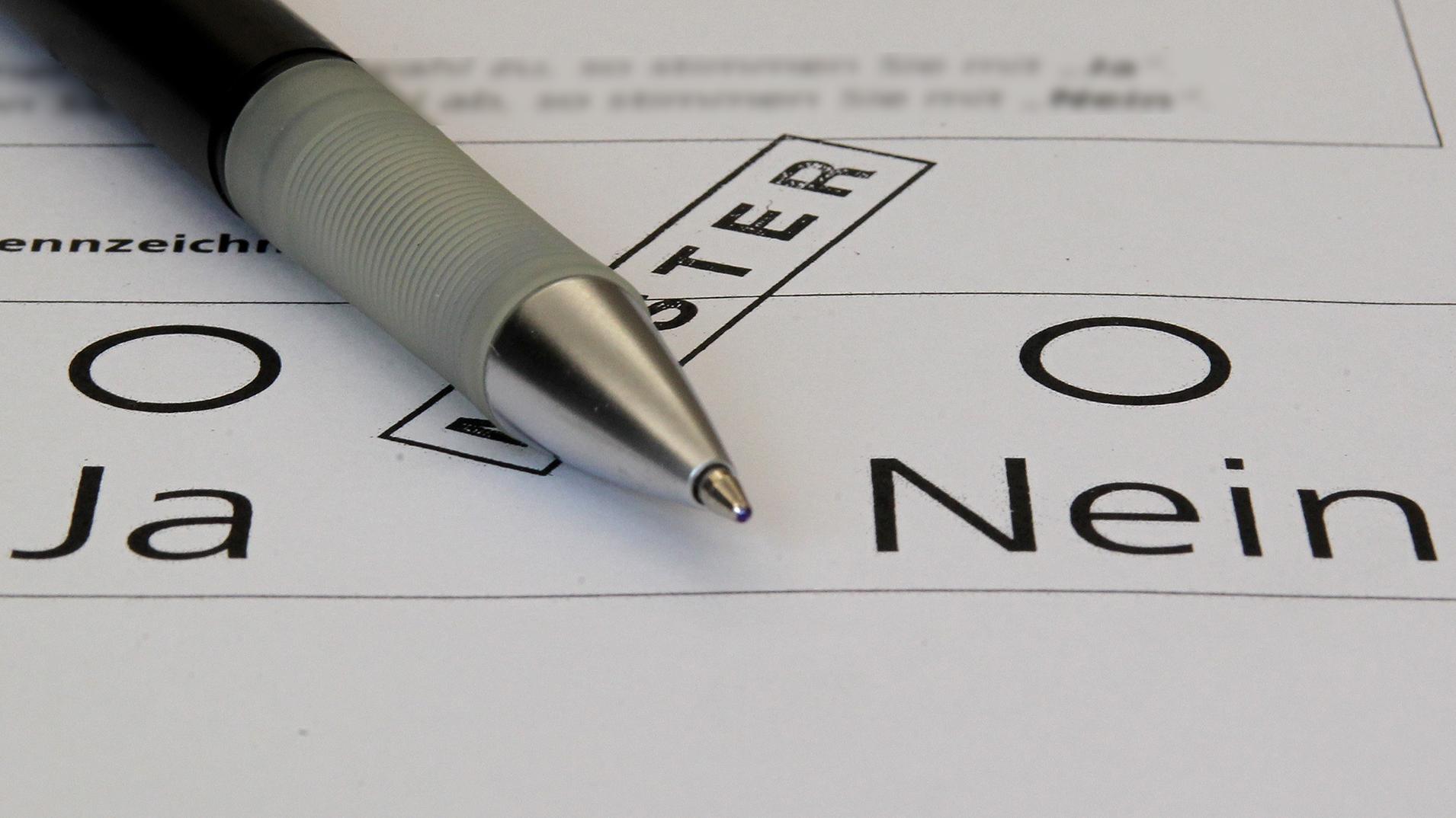 Ein Muster-Wahlzettel auf dem groß JA und NEIN zum Ankreuzen steht. In der Mitte liegt ein Kugelschreiber.