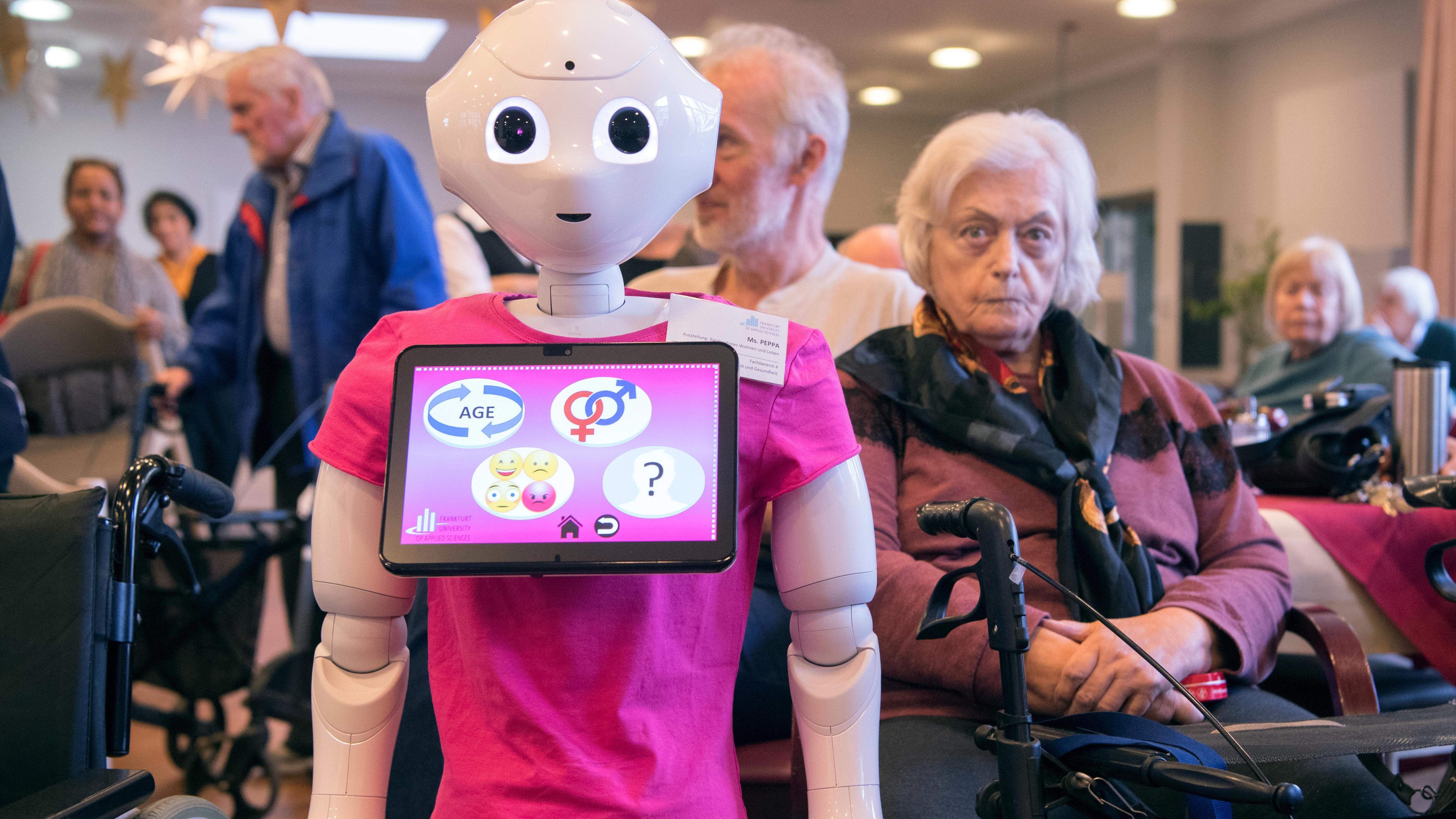 """Eine Seniorin sitzt neben dem humanoiden Roboter """"Pepper"""""""