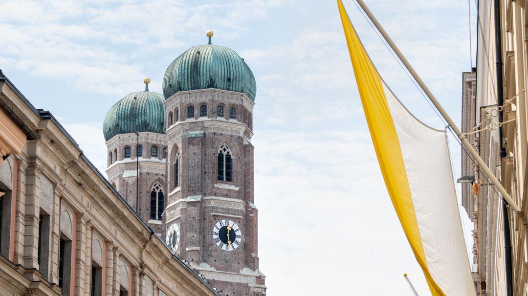 Eine Fahne mit den Farben der katholischen Kirche, gelb und weiß, ist vor den Türmen der Frauenkirche an der Fassade eines Hauses zu sehen.