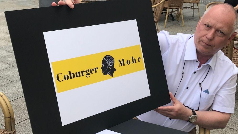 Detlef Beil hält ein Schild in den Händen, auf denen der Coburger Mohr abgebildet ist.   Bild:BR/Richard Krill