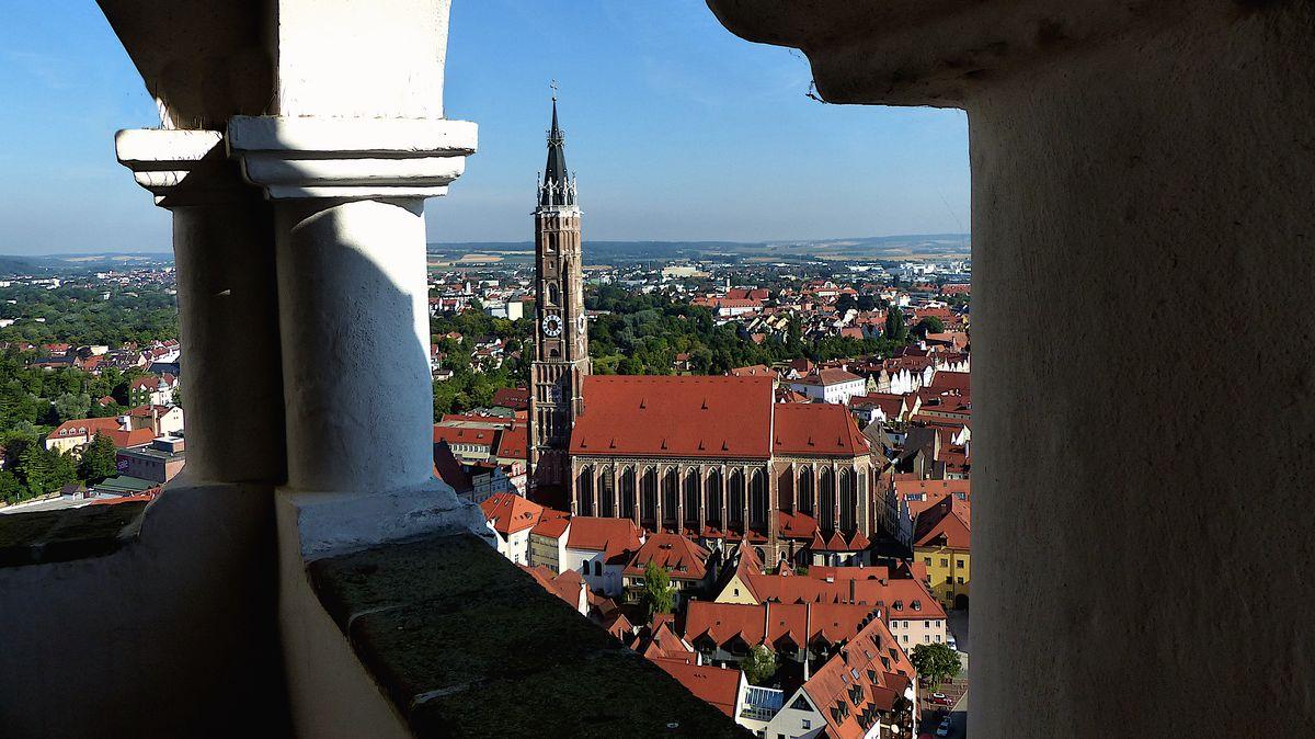 Der Blick durch eine Öffnung in der Burg Trausnitz auf die höchste Backsteinturm-Kirche Europas in Landshut
