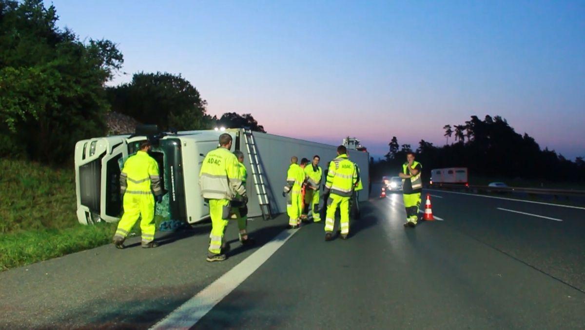 Ein Lastwagen liegt im Morgengrauen auf der Seite im Straßengraben. Mitarbeiter des ADAC stehen daneben.