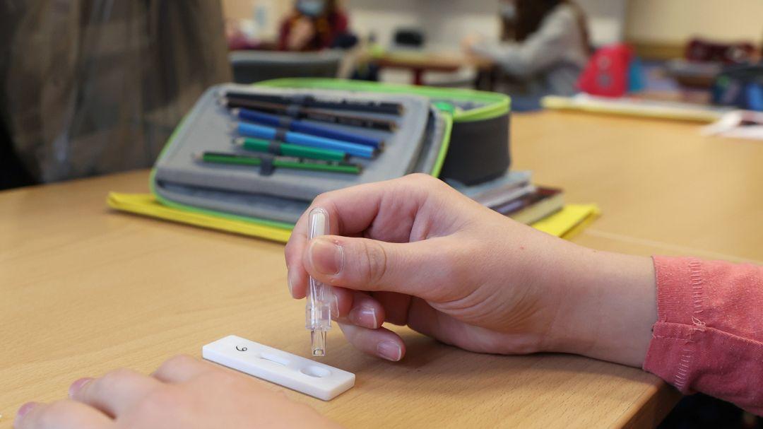 Eine Schülerin träufelt in einem Klassenraum eine Lösung nach einem selbst durchgeführten Corona-Test auf einen SARS-CoV-2-Antigentest.