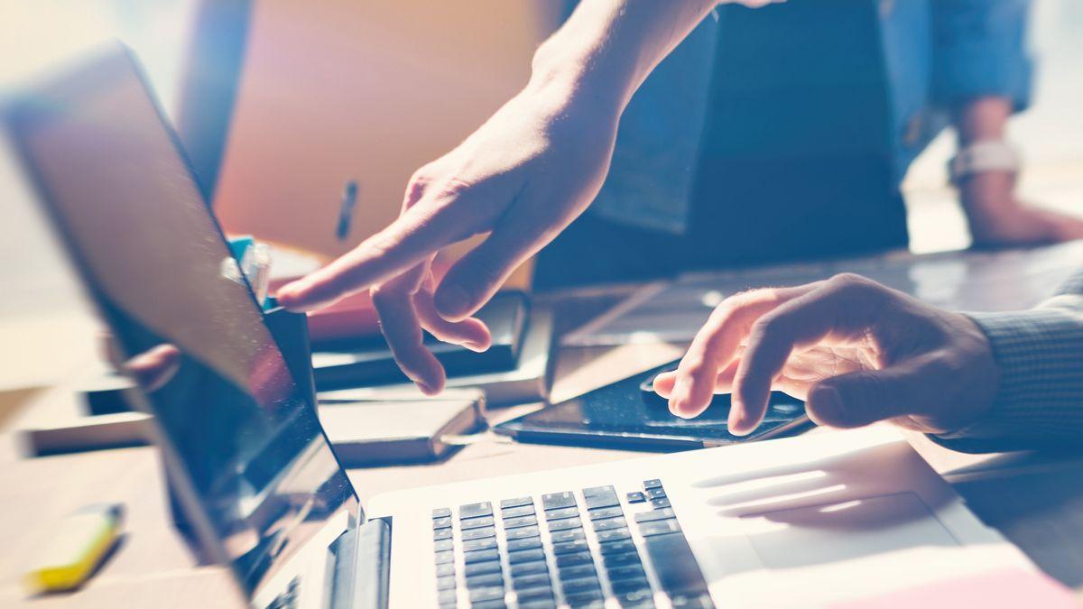 Zwei Menschen arbeiten zusammen an einem Laptop