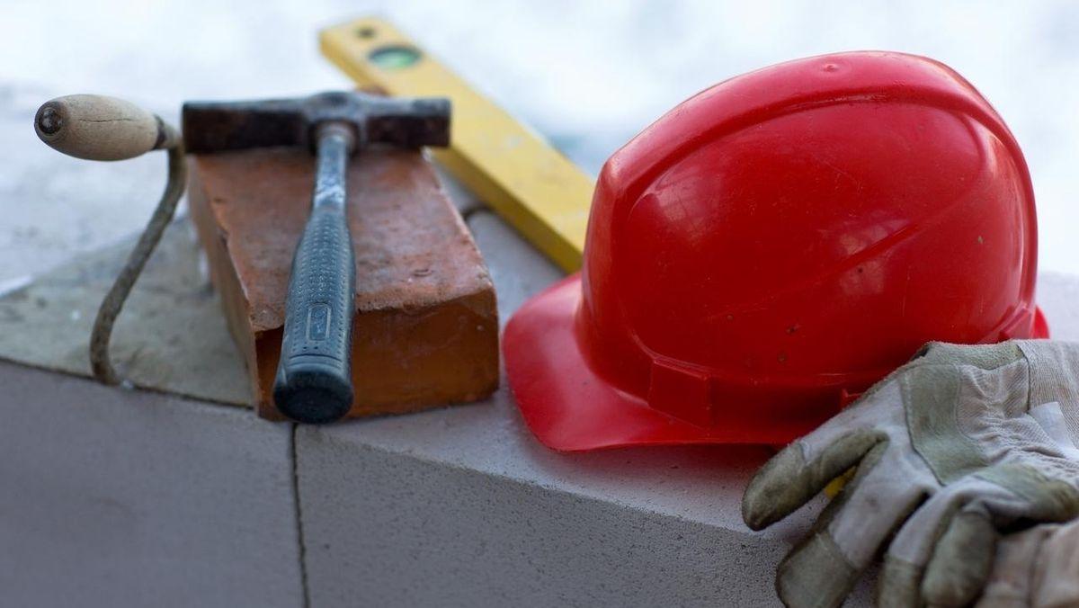 Handwerkszeug für die Baubranche liegt auf einer Mauer.