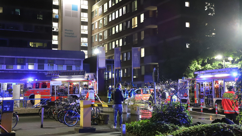 Düsseldorf: Einsatzkräfte der Feuerwehr stehen nach einem Brand im Marien Hospital vor dem Krankenhaus.