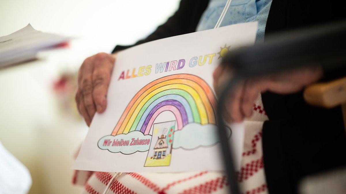 """Eine Seniorin hält ein gemaltes Bild mit der Aufschrift """"Alles wird gut"""" in den Händen (Symbolbild)"""