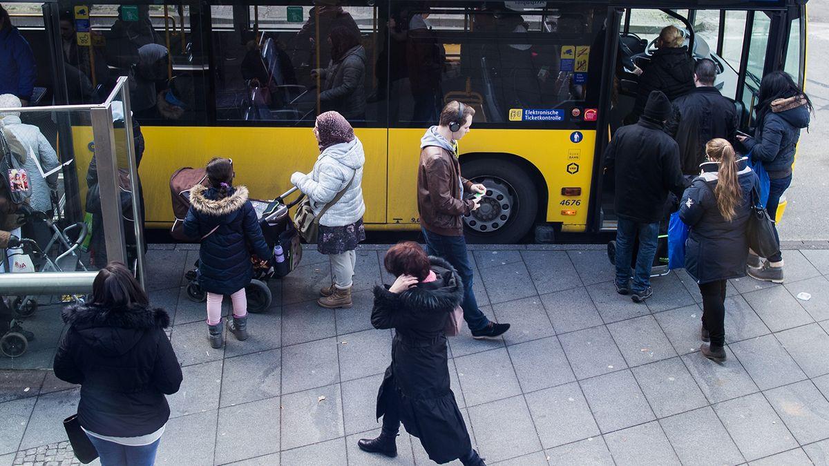 Ein Bus mit ein- und aussteigenden Menschen an einer Haltestelle