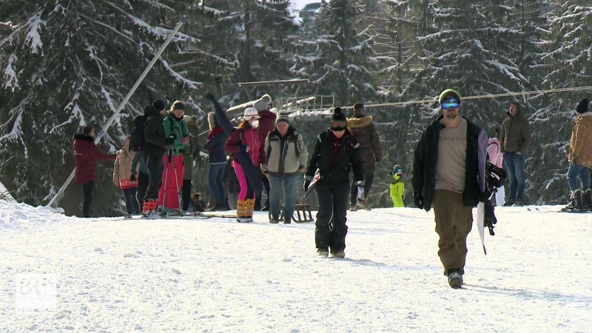 Spaziergänger und Wanderer mit und ohne Maske marschieren über eine Pist, dahinter verschneite Bäume.