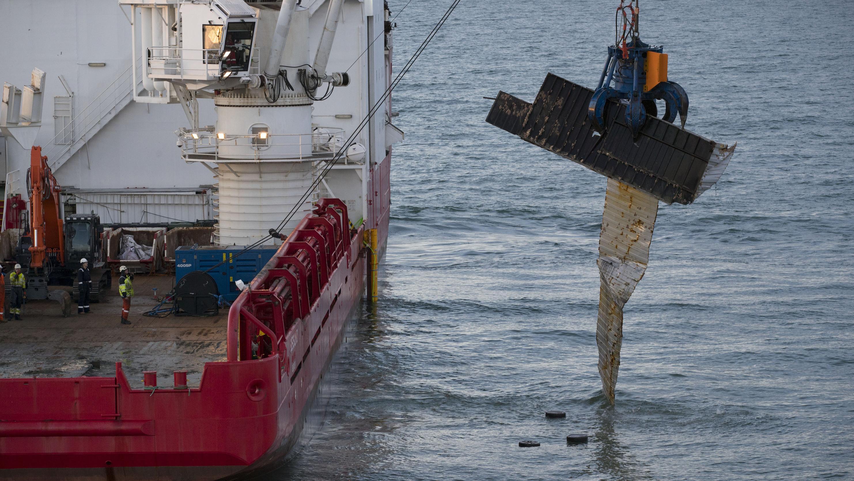 Ein Bergungsschiff hebt einen Container aus dem Wasser.