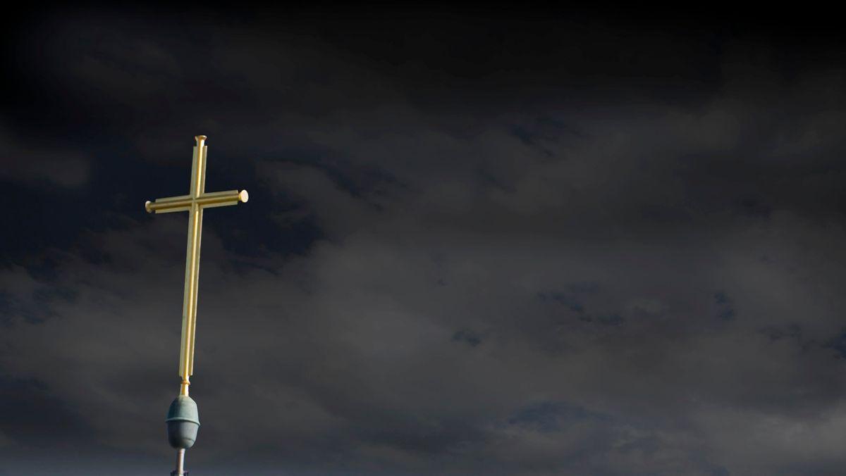 Ein Kreuz vor einem dunklen, bewölkten Himmel