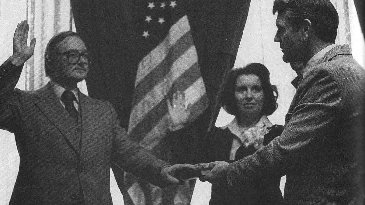 Eine Schwarzweiß-Aufnahme eines Mannes, der unter der Flagge Amerikas schwört.
