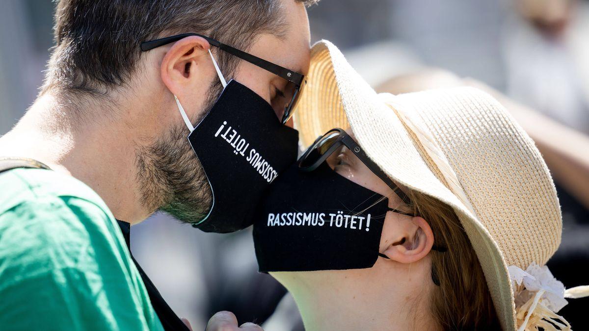 """Ein Mannn und eine Frau tragen einen schwarzen Mundschutz mit der Aufschrift, """"Rassismus tötet!"""" auf einer Demonstration"""