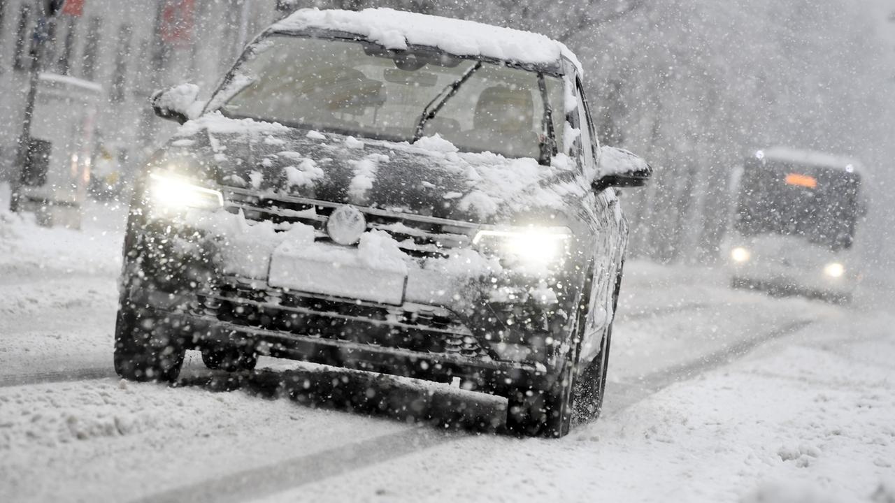Ein Auto fährt bei Schneefall auf einer schneebedeckten Straße.