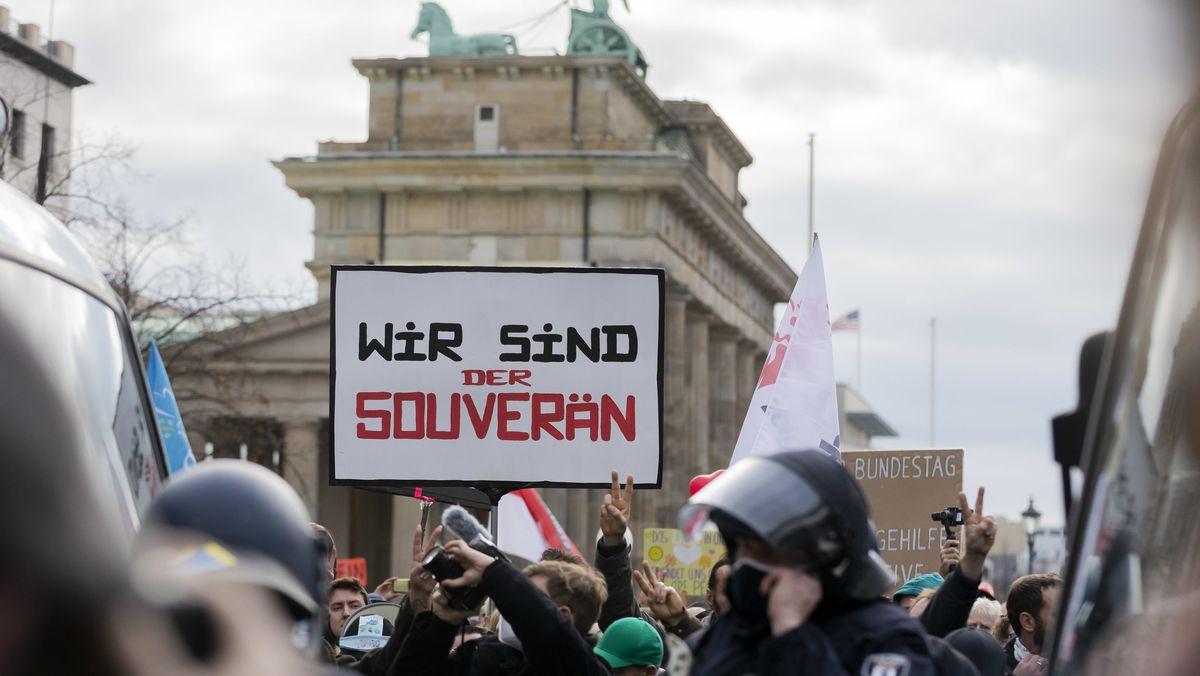 """Demonstranten mit einem Schild """"Wir sind der Souverän"""" und Polizisten vor dem Brandenburger Tor"""