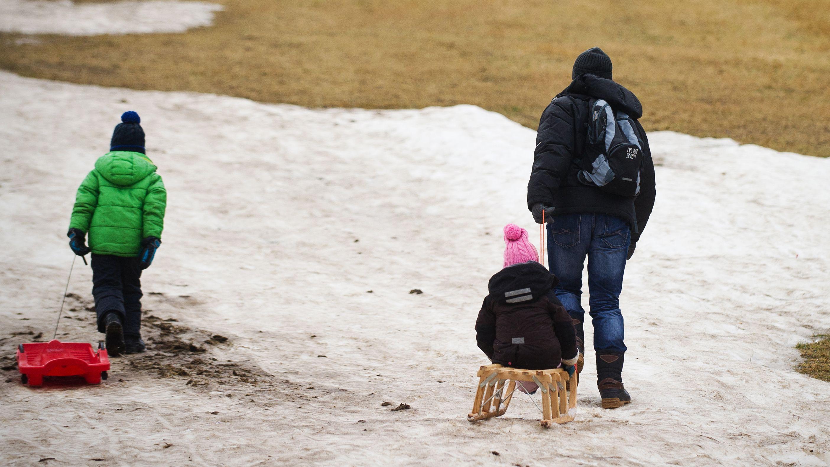 Familie beim Schlittenfahren, nur ein Teil des Berges ist mit Schnee bedeckt