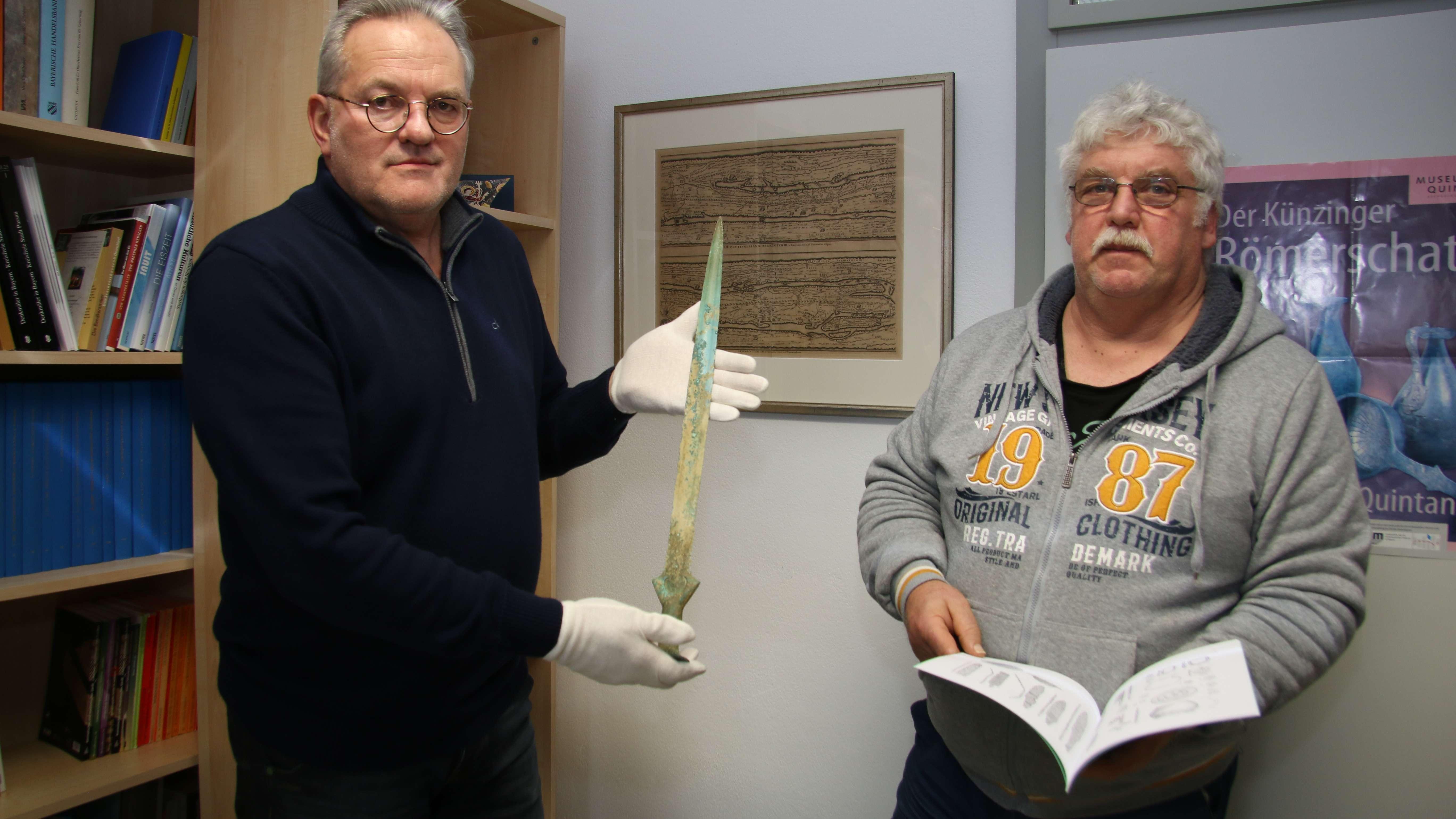 Kreisarchäologe Walter Wandling (links) mit dem Schwert und Mitarbeiter der Kreisarchäologie Reinhard Baumgartner