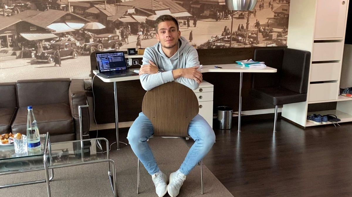 Student Marcel M. sitzt auf einem Stuhl in seinem Hotelzimmer.
