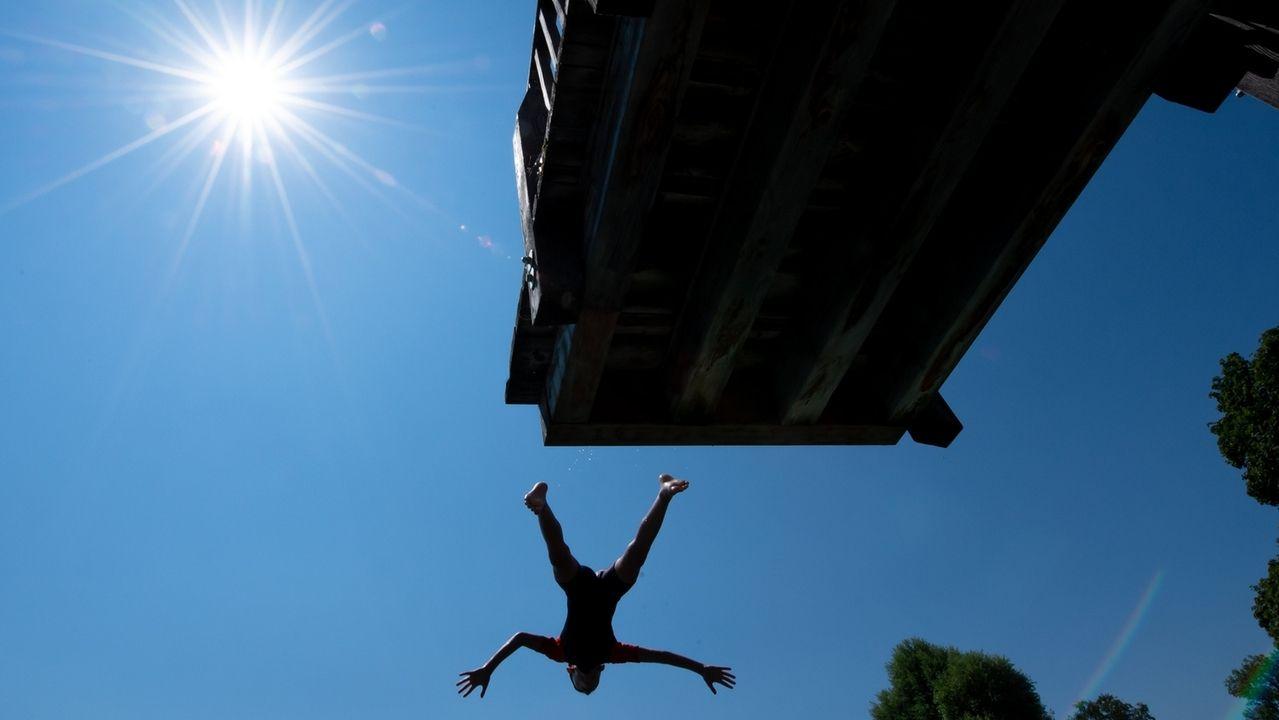 Ein Junge springt im Strandbad Utting bei Sonnenschein und hohen Temperaturen in den Ammersee.