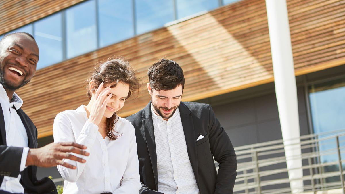 Drei Geschäftsleute lachen vor einem Gebäude.