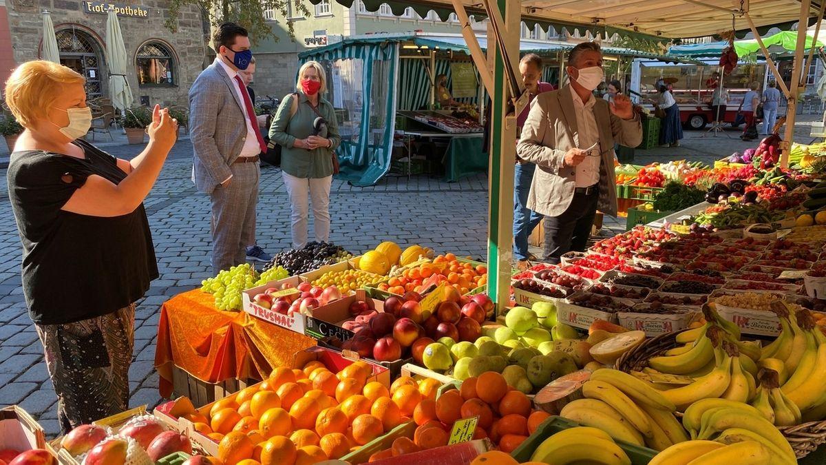 Auf dem Coburger Wochenmarkt stehen Personen mit Mund-Nasenschutz vor einem Obststand mit unter anderem Beeren, Orangen und Bananen.