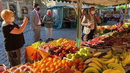 Auf dem Coburger Wochenmarkt stehen Personen mit Mund-Nasenschutz vor einem Obststand mit unter anderem Beeren, Orangen und Bananen.  | Bild:BR/Markus Klingele