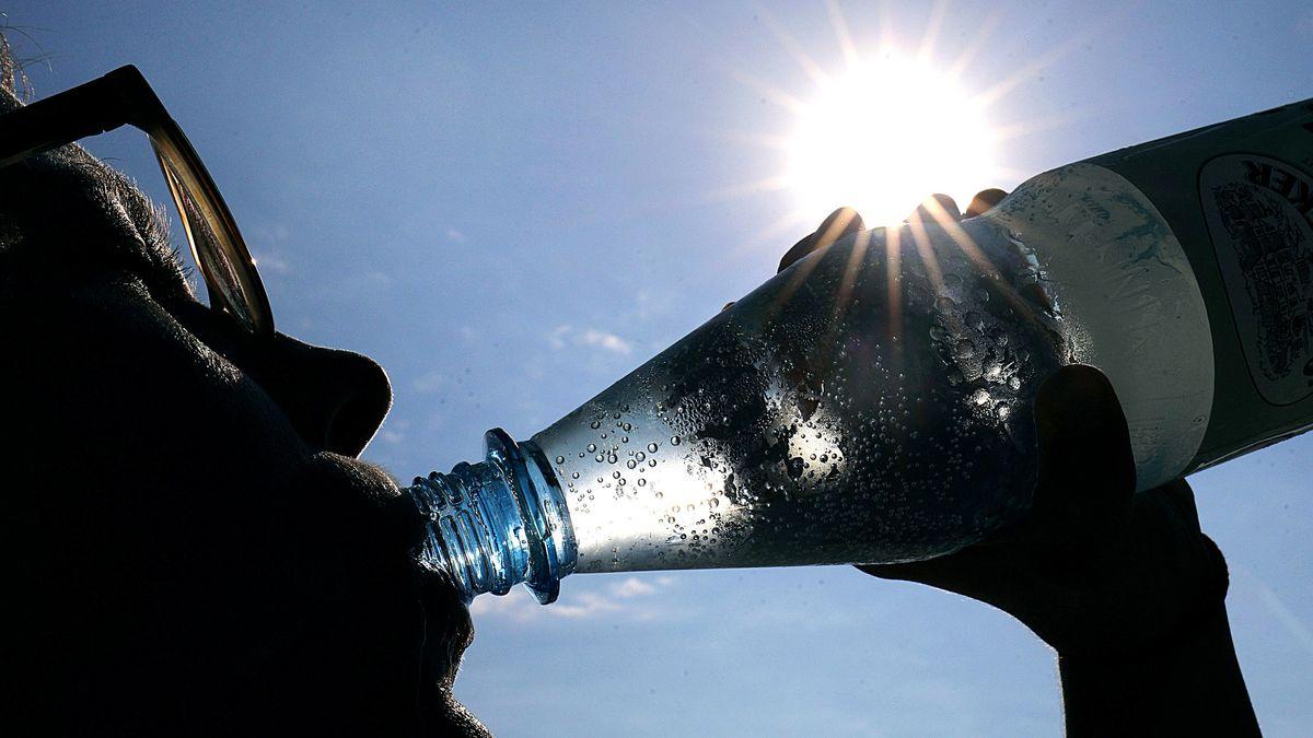 Frau trinkt aus einer Flasche Wasser