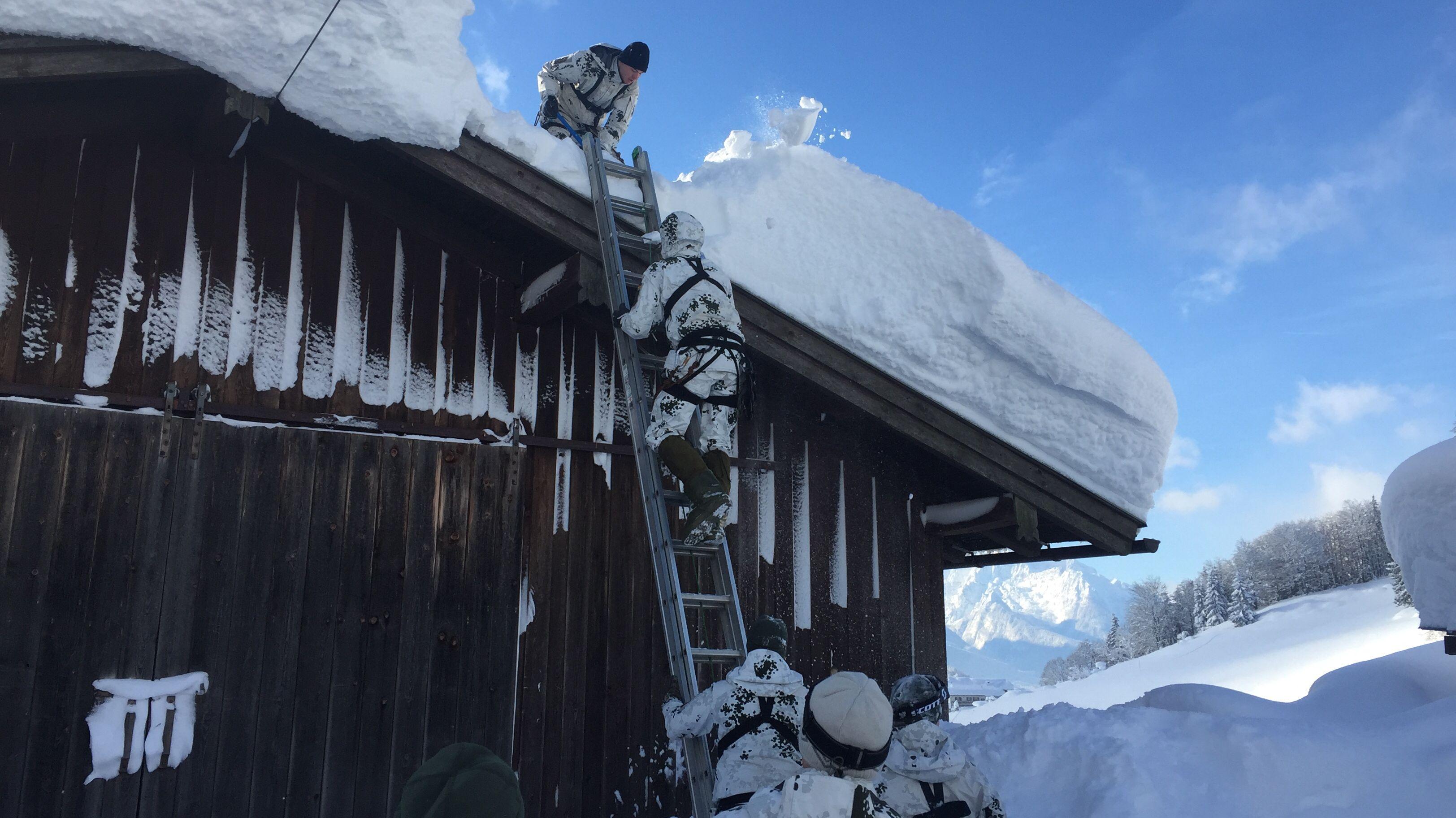 Bundeswehr-Soldaten steigen mit einer Leiter auf das Dach einer Scheune in Berchtesgaden und befreien es vom Schnee.